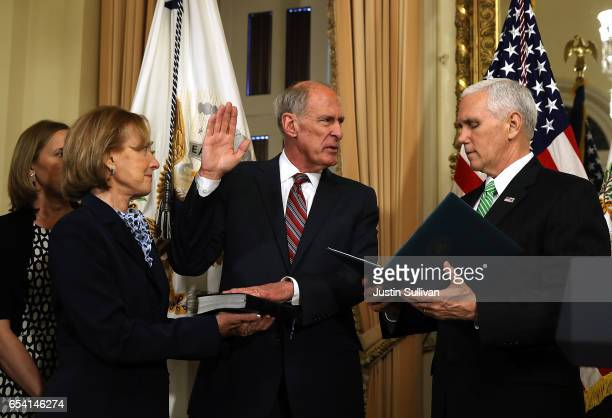 S Vice President Mike Pence administers the oath of office to new National Intelligence Director Dan Coats as Marsha Coats looks on during a...