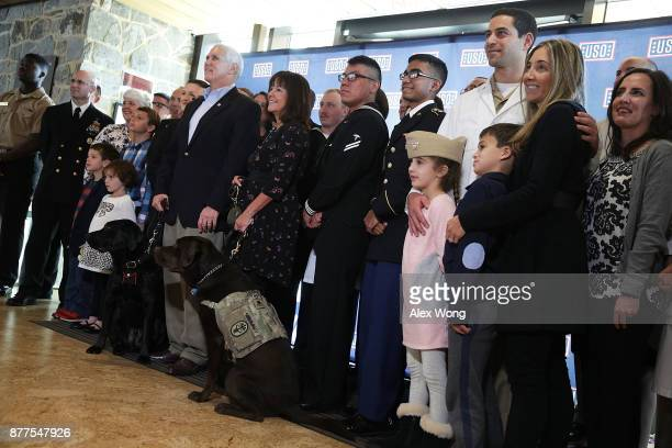 S Vice President Mike Pence and his wife Karen Pence participate in a group photo at the USO Warrior and Family Center November 22 2017 in Bethesda...