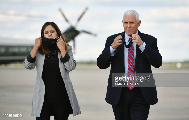 Vice President Mike Pence and his wife Karen Pence take their facemasks off as Pence approaches the media to speak at Andrews Air Force Base in...