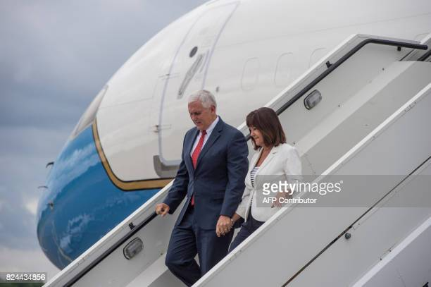US Vice President Mike Pence and his wife Karen Pence wave as they disembark their plane after arriving at the airport in Tallinn Estonia on July 30...