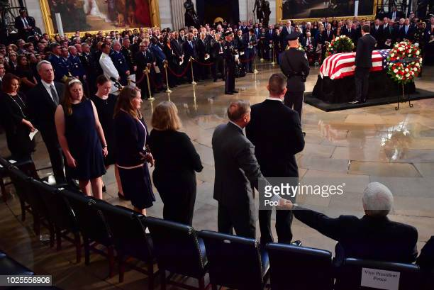 S Vice President Mike Pence and Sen Lindsey Graham hold hands with a view of the casket of former Senator John McCain in the Capitol Rotunda where he...