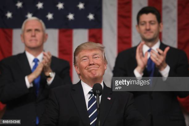 Vice President Mike Pence and Speaker of the House Paul Ryan applaud as US President Donald J Trump delivers his first address to a joint session of...