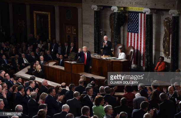 US Vice President Mike Pence and Speaker of the US House of Representatives Nancy Pelosi listen to US President Donald Trump deliver the State of the...