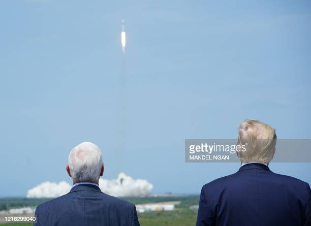Vice President Mike Pence and US President Donald Trump watch the SpaceX Falcon 9 rocket carrying the SpaceX Crew Dragon capsule with astronauts Bob...