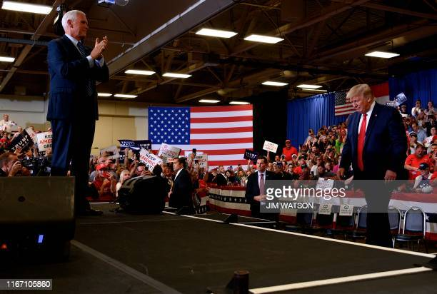 """Vice President Mike Pence applauds after introducing US President Donald Trump as he arrives to speak to a """"Keep America Great"""" campaign rally at The..."""