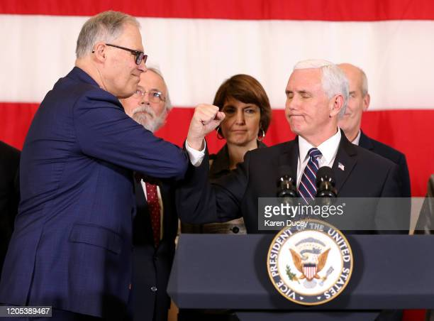 US Vice President Mike Pence bumps arms with Washington State Governor Jay Inslee during a press conference on March 5 2020 at Camp Murray adjacent...