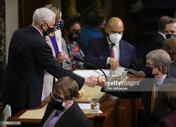 Vice President Mike Pence bumps fists with U.S. Sen. Roy Blunt at the conclusion of the count of electoral votes in the House Chamber during a...
