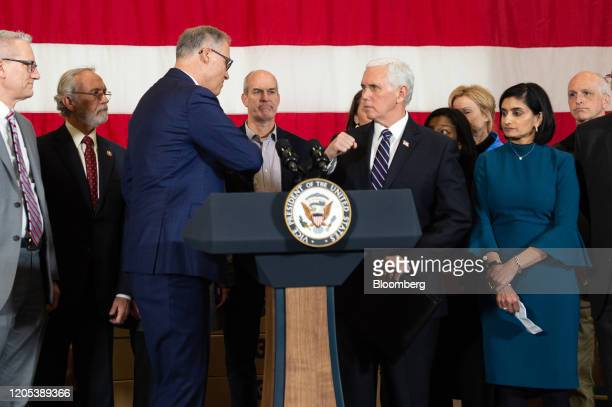 US Vice President Mike Pence center right greets Jay Inslee governor of Washington center left during a joint news conference at Camp Murray in...