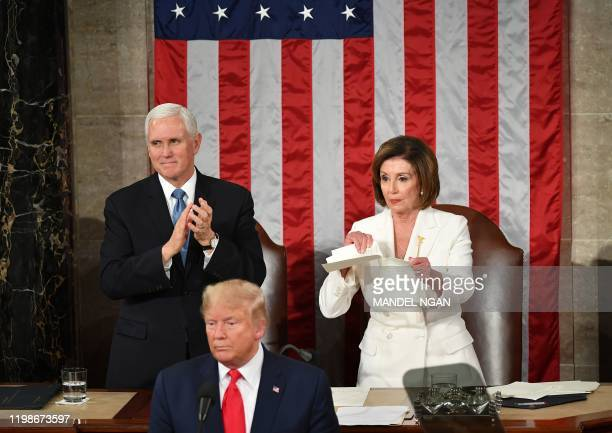 US Vice President Mike Pence claps as Speaker of the US House of Representatives Nancy Pelosi appears to rip a copy of US President Donald Trump...