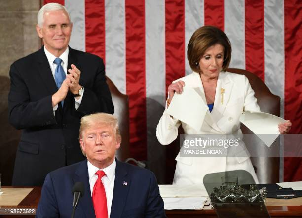Vice President Mike Pence claps as Speaker of the US House of Representatives Nancy Pelosi appears to rip a copy of US President Donald Trumps speech...