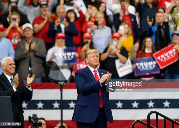 Vice President Mike Pence claps as U.S. President Donald Trump takes the stage during a campaign rally at the Target Center on October 10, 2019 in...