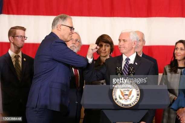 Vice President Mike Pence gestures with Washington State Governor Jay Inslee during a press conference on March 5 2020 at Camp Murray adjacent to...