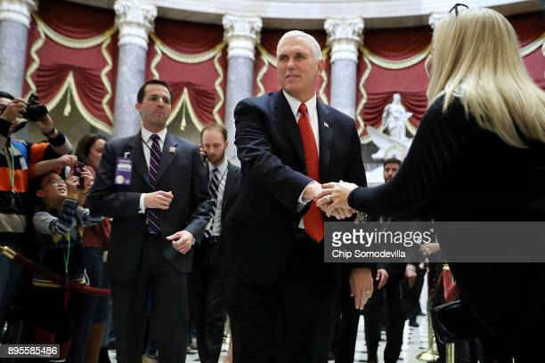 Vice President Mike Pence greets people as he walks through Statuary Hall on his way to the House of Representatives for the vote on the Tax Cuts and...