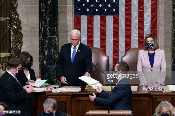 Vice President Mike Pence hands the West Virginia certification to staff as Speaker of the House Nancy Pelosi, D-Calif., listen during a joint...