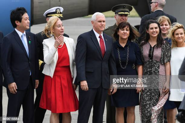 US Vice President Mike Pence his wife Karen and two daughters Audrey and Charlotte pose for photographs after arriving at the US naval air facility...