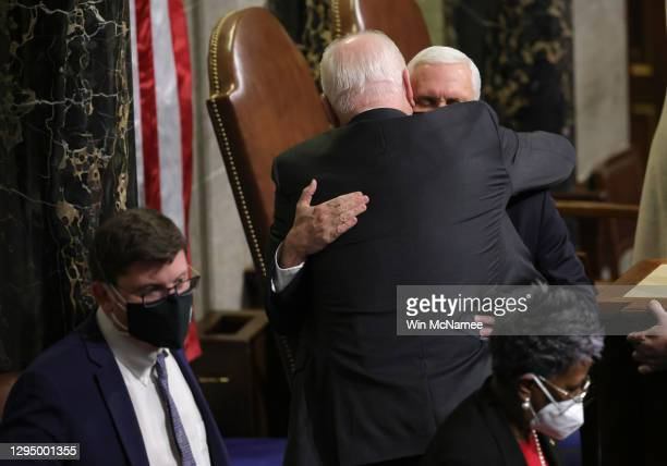 Vice President Mike Pence is hugged at the conclusion of the count of electoral votes in the House Chamber during a reconvening of a joint session of...