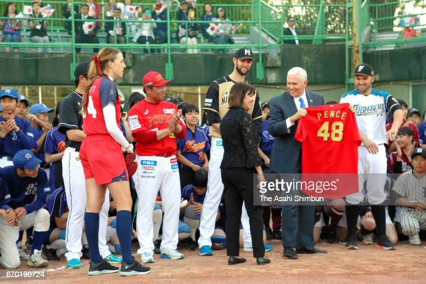 US Vice President Mike Pence is presented an uniform from former major league player and head coach of baseball team Fukushima Hopes Akinori Iwamura...
