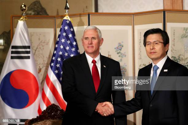 US Vice President Mike Pence left shakes hands with Hwang Kyoahn South Korea's acting president and prime minister ahead of a meeting in Seoul on...