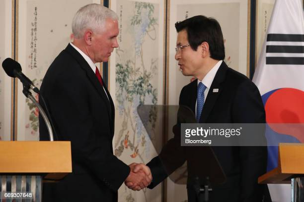 US Vice President Mike Pence left shakes hands with Hwang Kyoahn South Korea's acting president and prime minister during a joint news conference...
