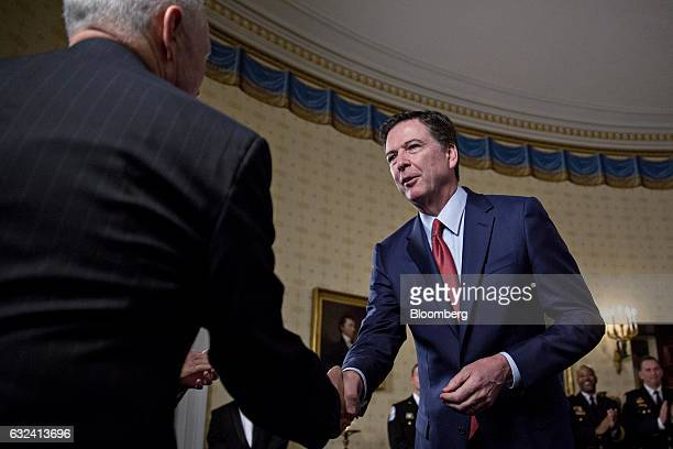 US Vice President Mike Pence left shakes hands with James Comey director of the Federal Bureau of Investigation during an Inaugural Law Enforcement...