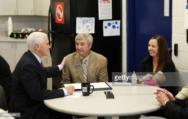 US Vice President Mike Pence left speaks with dairy farmer Hank Choate center and his daughter Stacey Hughes during an event at the American Axle...