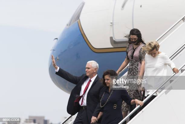 US Vice President Mike Pence left waves as second lady Karen Pence bottom right and his daughters Audrey top left and Charlotte walk down the steps...
