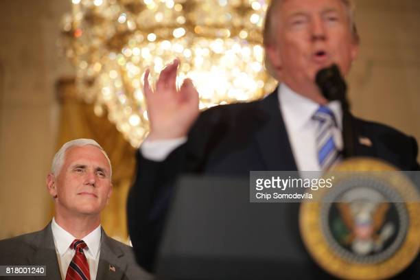 S Vice President Mike Pence listens to President Donald Trump deliver remarks during a Made in America product showcase with in the East Room of the...
