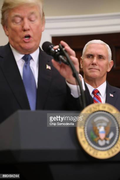 S Vice President Mike Pence listens to President Donald Trump deliver remarks before signing 'Space Policy Directive 1' in the Roosevelt Room at the...