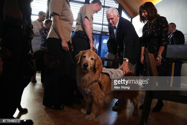 S Vice President Mike Pence pats a facility dog as his wife Karen Pence looks on at the USO Warrior and Family Center November 22 2017 in Bethesda...