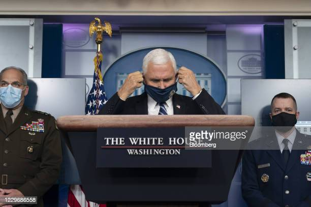 Vice President Mike Pence puts on a protective mask during a news conference in the White House in Washington, D.C., U.S., on Thursday, Nov. 19,...