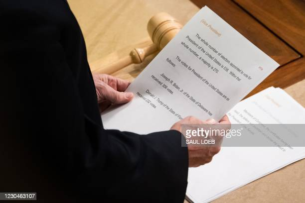 Vice President Mike Pence reads a sheet of paper with the final electoral vote counts declaring Joe Biden as the next US President during a joint...
