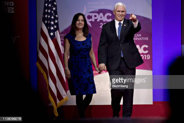 US Vice President Mike Pence right gestures while arriving to speak with US Second Lady Karen Pence during the Conservative Political Action...