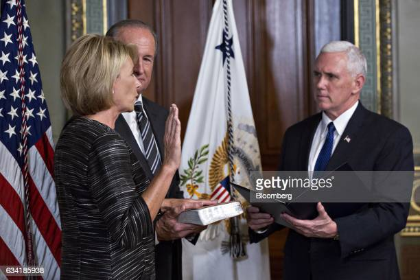 US Vice President Mike Pence right swears in Betsy DeVos as US secretary of education left as her husband Dick DeVos Jr holds the Bible inside the...