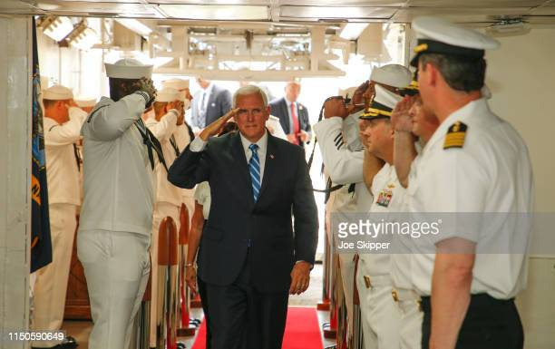 S Vice President Mike Pence salutes as he is welcomed aboard the US Navy hospital ship USNS Comfort at the Port of Miami prior to a tour of the...