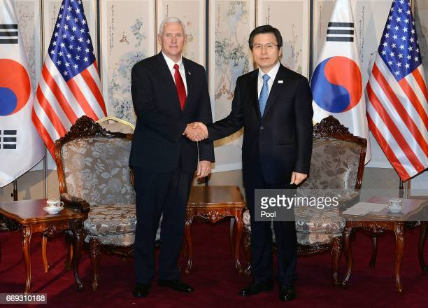 US Vice President Mike Pence shakes hands with South Korean acting president and prime minister Hwang Kyoahn during their meeting on April 17 2017 in...