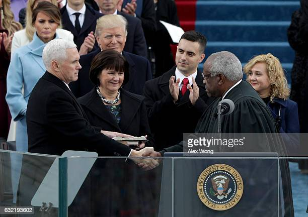 Vice President Mike Pence shakes hands with Supreme Court Justice Clarence Thomas as wife Karen Pence holds a bible on the West Front of the U.S....