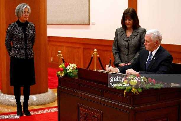 S Vice President Mike Pence signs a guestbook as his wife Karen Pence and Kang Kyungwha the Minister of Foreign Affairs of South Korea look on...