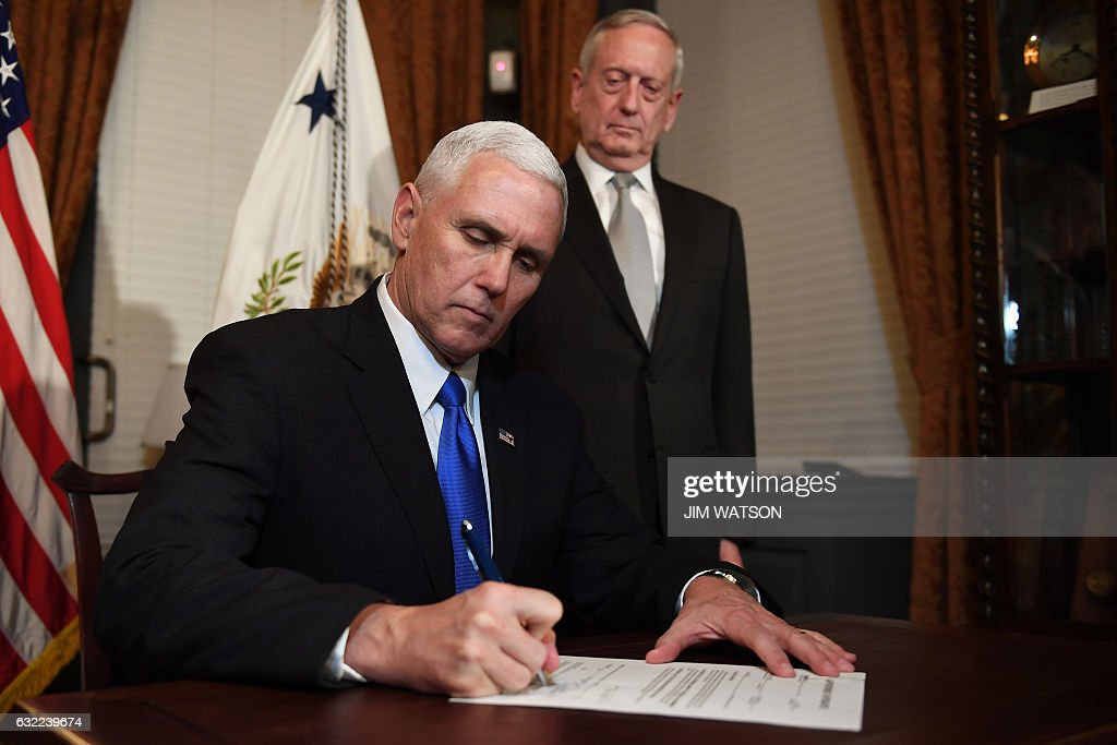 US Vice President Mike Pence (L) signs James Mattis' (L) confirmation letter after swearing him in as the US Secretary of Defense in the Vice President's Ceremonial Office in the Old Executive Office Building in Washington, DC, January 20, 2017. / AFP / JIM