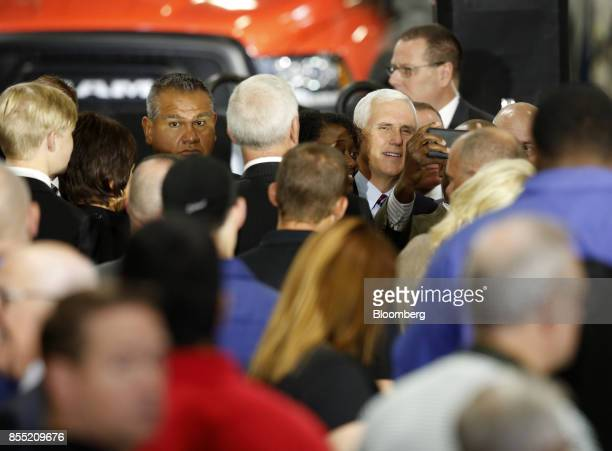 US Vice President Mike Pence smiles for a photograph with an attendee during an event at the American Axle Manufacturing Inc facility in Auburn Hills...