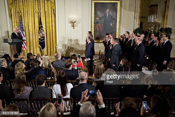 S Vice President Mike Pence stands next to US President Donald Trump as Pence swears in senior staff members during a ceremony in the East Room of...