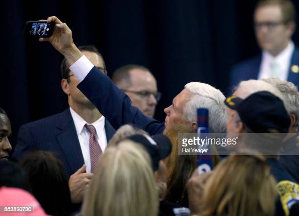 Vice President Mike Pence takes a selfie with supporters at a campaign rally for Sen Luther Strange at HealthSouth Aviation on September 25 2017 in...