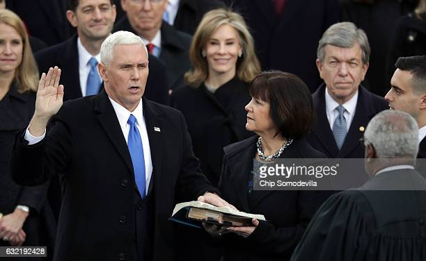 S Vice President Mike Pence takes the oath of office from Supreme Court Justice Clarence Thomas as his wife Karen Pence holds the Bible on the West...