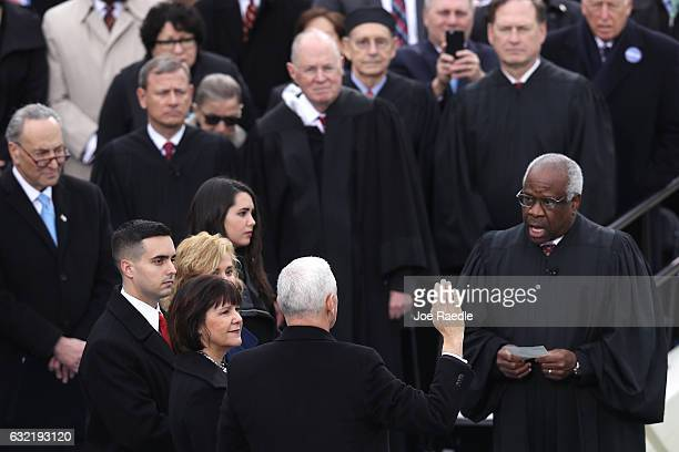 Vice President Mike Pence takes the oath of office from Supreme Court Justice Clarence Thomas as wife Karen Pence holds a bible on the West Front of...
