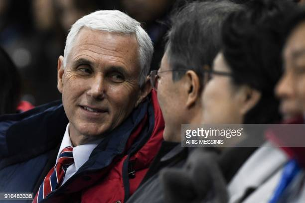 Vice President Mike Pence talks to South Korea's President Moon Jae-in as they watch the short track speed skating heats during the Pyeongchang 2018...
