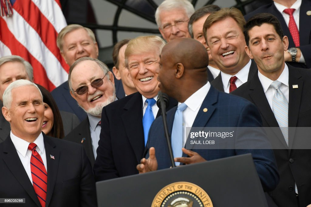 TOPSHOT - (2nd row From L to R) Vice President Mike Pence, US President Donald Trump and House speaker Paul Ryan listen as Republican Senator Tim Scott (foreground) speaks about the passage of tax reform legislation on the South Lawn of the White House in Washington, DC, December 20, 2017. /
