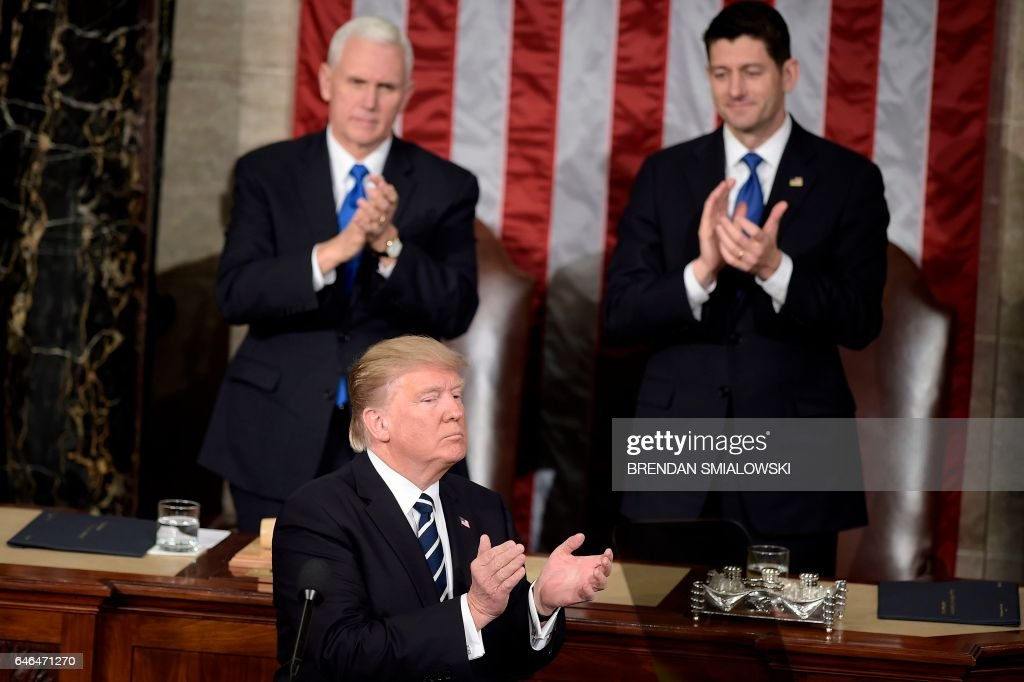 Vice President Mike Pence (L), US President Donald Trump (C) and Speaker of the House Paul Ryan (R-WI) clap during a joint session of Congress on Capitol Hill February 28, 2017 in Washington, DC. / AFP PHOTO / Brendan Smialowski