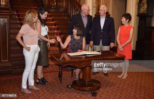 US Vice President Mike Pence watches his wife Karen sign the visitors book at Government House along with his daughters Charlotte and Audrey and the...