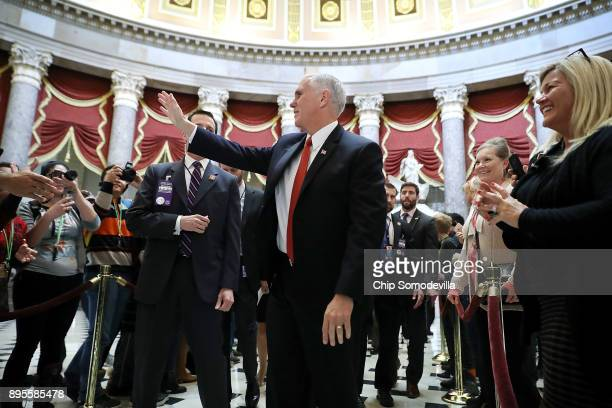 Vice President Mike Pence waves to people as he walks through Statuary Hall on his way to the House of Representatives for the vote on the Tax Cuts...
