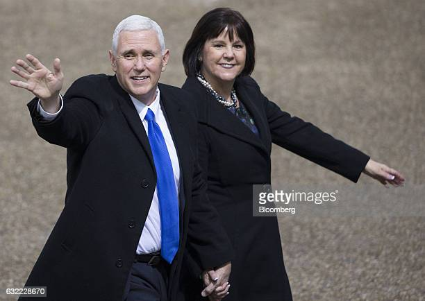 US Vice President Mike Pence waves while walking with Second Lady Karen Pence near the White House during the 58th presidential inauguration parade...