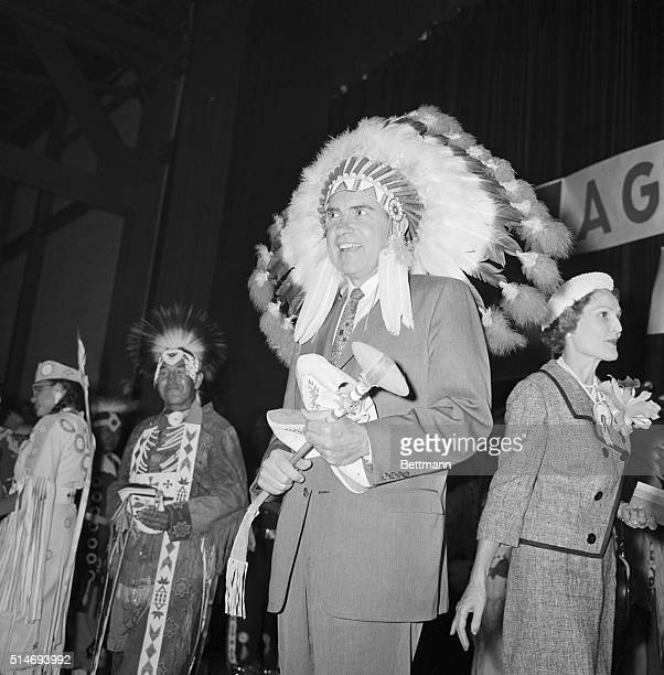 Vice President Nixon wears a feather headdress and carries a tomahawk at a native American reservation in Minot North Dakota The tomahawk and...